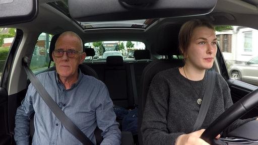 Fahrlehrer mit Fahrschülerin im Auto.