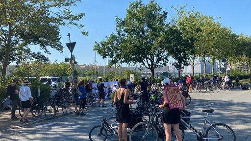 Eine Gruppe Menschen steht mit Fahrrädern vor dem Mercedes-Werk in Bremen.