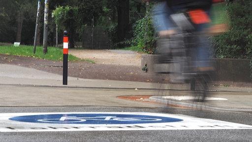 Eine Fahrradfahrerin fährt über ein aufgemaltes Fahrradstraßen Piktogram in der Bremer Neustadt.