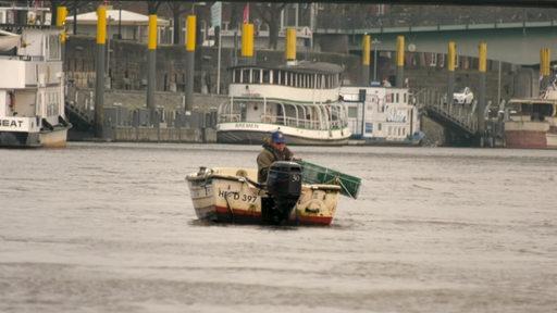 Ein Fischer mit einem kleinem Boot auf der Weser beim angeln
