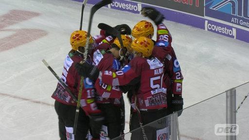 Vier Eishockey-Spieler der Fischtown Pinguins auf dem Eishockey-Feld, die sich die Köpfe zusammendrücken und sich umarmen.
