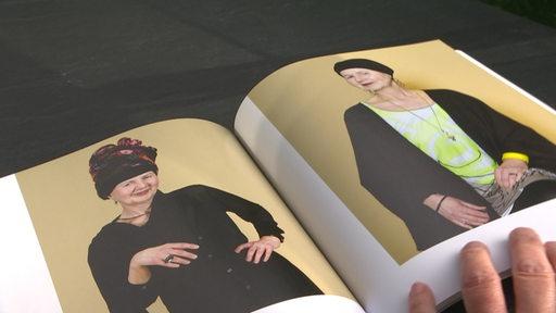 Ein aufgeklappter Fotokatalog mit zwei Bildern von krebskranken Frauen.