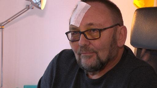 AfD- Politiker Frank Magnitz mit großem Pflaster auf der Stirn.
