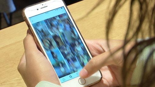Eine jungen Frau guckt sich Fotos auf einem Smartphone an.