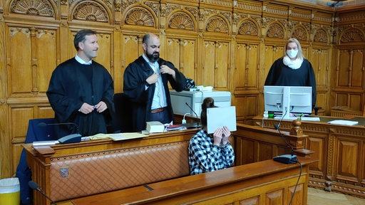 Eine Angeklagte hät sich in einem Gerichtssaal eine weiße Mappe vor das Gesicht.