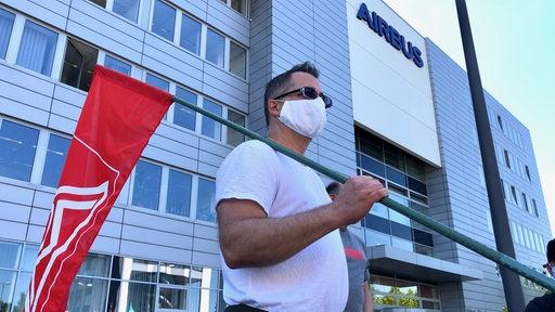 Ein IG-Metall-Mitglied steht mit einer roten Fahne in der Hand vor einem Airbus-Gebäude in Bremen.