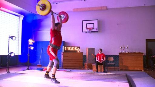 Ein Gewichtheber mit roten Anzug stemmt eine Hantelstange mit Gewichten.