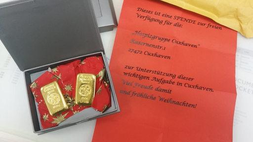 Zwei Goldbarren in einem Schächtelchen mit einem Schreiben, dass es sich um eine Spende handelt.