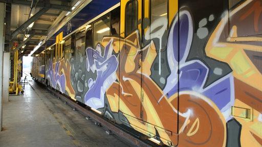Ein mit Graffiti besprühter Zug steht in einer Werkstatt.
