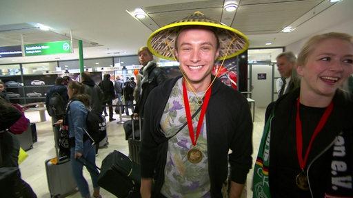 Ein Tänzer des Grün-Gold-Clubs mit breitem Grinsen und einem chinesischen Hut auf dem Kopf bei der Ankunft am Bremer Flughafen.