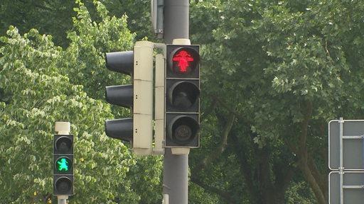 Eine Fußgängerampel zeigt Rot, eine andere dahinter Grün.