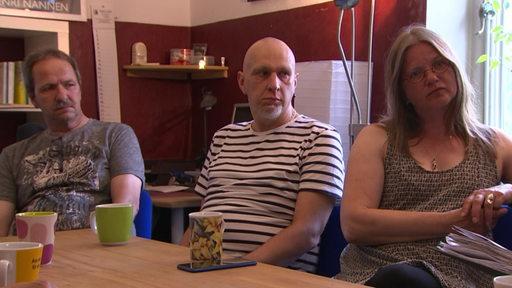 Drei Personen sitzen an einem Tisch mit Kaffebechern.