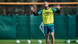 Ömer Toprak hält auf dem Trainingsplatz abwehrend die Arme empor.