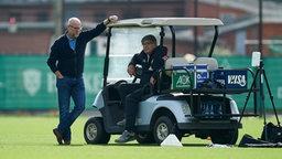 Thomas Schaaf lehnt am Golfcart und unterhält sich mit Holger Berger.