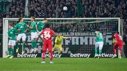 Ein Ball fliegt Richtung Werder-Tor und Jiri Pavlenka.