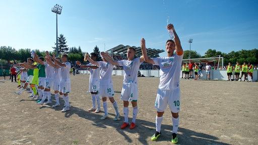 Die Werder-Spieler stehen aufgereiht vor der Bremer Fankurve in Worms und reißen die Arme hoch.