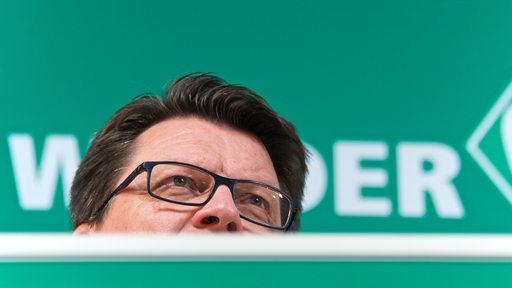 Hess-Grunewald auf dem Podium der Pressekonferenz aus der Froschperspektive fotografiert.