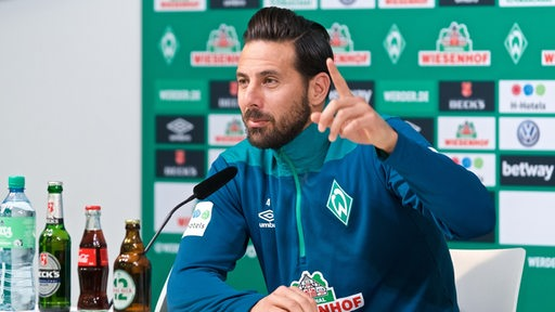 Claudio Pizarro hebt auf dem Podium der Pressekonferenz den Zeigefinger.
