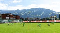 Panoramablick im Zillertal über Werders Trainingsplatz mit Bergkette im Hintergrund.