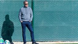 Marco Bode beobachtet mit dunkler Sonnenbrille und Händen in den Hosentaschen das Werder-Training.