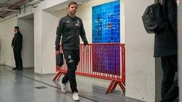 Florian Kohfeldt erscheint nach seiner Fußverletzung ohne sichtliche Probleme in den Katakomben des Düsseldorfer Stadions.