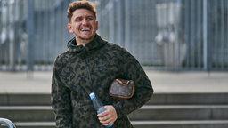 Milos Veljkovic läuft in Freizeitkleidung am Weser-Stadion entlang und lacht.