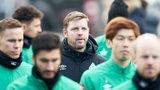 Florian Kohfeldt nachdenklich inmitten seiner Spieler auf dem Weg zum Trainingsplatz.