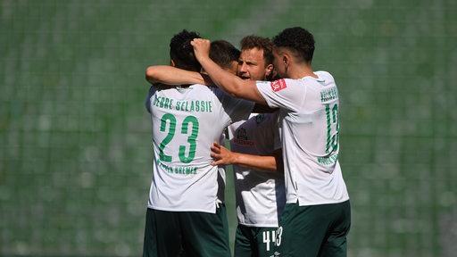Mehrer Werder-Spiele liegen sich jubelnd in den Armen.