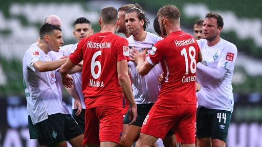 Werders und Heidenheims Spieler liefern sich Wortgefechte.
