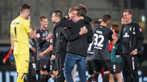 Florian Kohfeldt und Frank Baumann umarmen sich glücklich nach dem Heidenheim-Spiel.
