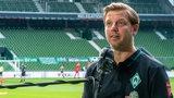 Werder-Trainer Florian Kohfeldt steht in einem leeren Stadion und spricht in ein Mikrofon.