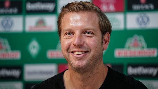 Werder-Coach lächelt in die Kamera.