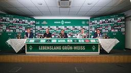 Werder-Verantwortliche sitzen auf dem Podium.