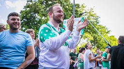 Werder-Fans stehen glücklich vor dem Weser-Stadion nach dem 6:1-Sieg gegen Köln.