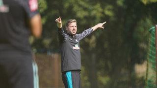 Florian Kohfeldt streckt auf dem Trainingsplatz seine Arme nach rechts und links aus, um seinen Spielern etwas zu erklären.