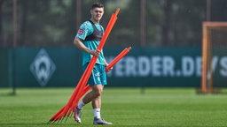 Milot Rashica trägt auf dem Trainingsplatz ein paar rote Stangen zu Seite.