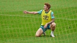 Joshua Sargent hockt mit gelbem Leibchen auf dem Rasen des Trainingsplatzes und deutet mit dem rechten Arm zur Seite.