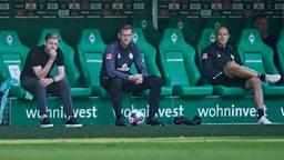 Florian Kohfeldt, Tim Borowski und Christian Vander sitzen nachdenklich beim Bundesligastart auf der Trainerbank.