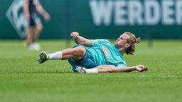 Niclas Füllkrug liegt im Training mit schmerzverzerrtem Gesicht am Boden.
