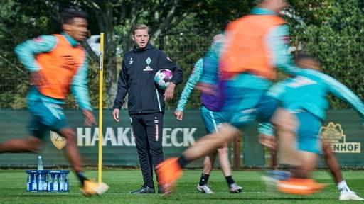 Florian Kohfeldt überwacht das Training, seine Spieler sind in der Unschärfe zu sehen.