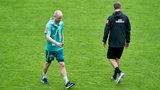 Davy Klaassen geht mit gesenktem Blick auf dem Trainingsplatz an Trainer Florian Kohfeldt vorbei.