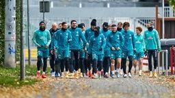 Werder-Spieler laufen zum Trainingsplatz.
