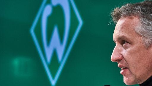 Frank Baumann sitzt auf dem Podium. Das Bild zeigt ihn von der Seite. Im Hintergrund ist eine Werder-Raute zu sehen.