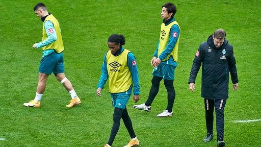 Milot Rashica, Tahith Chong, Yuya Osako und Florian Kohfeldt gehen nach einem Gespräch beim Training in verschiedene Richtungen auseinander.