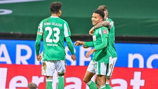 Felix Agu wird von seinem Mitspielern nach seinem ersten Treffer gegen Augsburg umarmt.