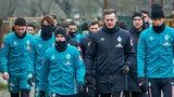 Werder-Spieler plus Co-Trainer Borowski und Torwarttrainer Vander laufen zum Trainingsplatz und schauen großteils auf den Boden.
