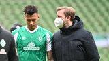 Florian Kohfeldt trägt einen Mund-Nasen-Schutz und spricht nach dem Leipzig-Spiel auf dem Rase mit Davie Selke, der in Richtung Boden blickt.