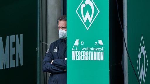 Werder-Sportchef Frank Baumann steht mit weißer FFP2-Maske und verschränkten Armen am Ausgang des Spielertunnels.