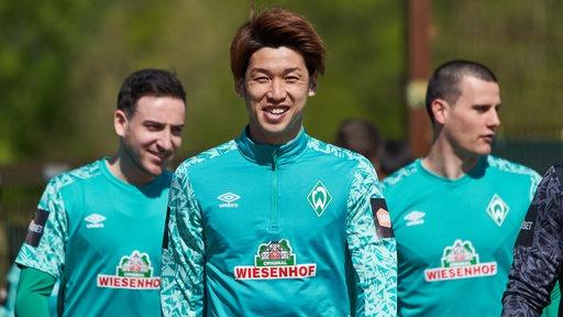 Werder-Spieler Yuya Osako mit strahlendem Lächeln auf dem Weg zum Trainingsplatz.