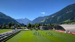 Blick auf Werders Trainingsplatz in Zell am Ziller vor dem Alpenpanorama bei strahlendem Sonnenschein und blauem Himmel.